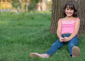 Sitting girl against the tree — Stock Photo