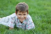 Garoto sorridente na grama verde — Fotografia Stock