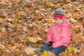 Serious little girl in the yellow leaves — Stock Photo