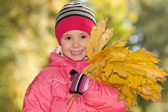 Happy little girl with yellow leaves — Stock Photo
