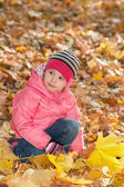Pensive little girl in the autumn park — Stock Photo