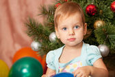 Little girl with big grey eyes at the fur tree — Stock Photo