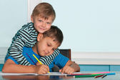 Two drawing boys at the desk — Foto Stock