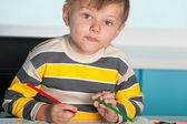 Säker liten pojke sitter vid skrivbordet — Stockfoto