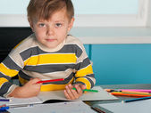 Serious little boy at the desk — Fotografia Stock