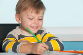 Little boy draws at the desk — Stock Photo