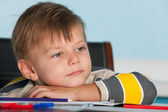 A thoughtful little boy at the desk — Stock Photo