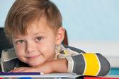 Porträtt av en leende pojke vid skrivbordet — Stockfoto
