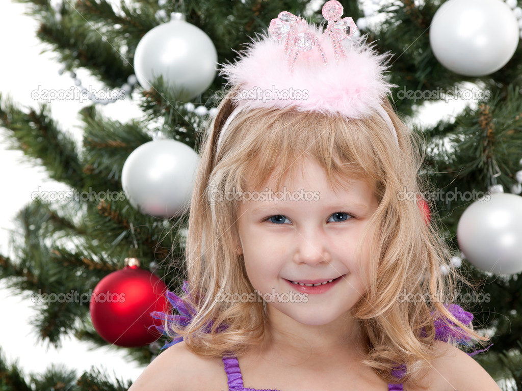 A portrait of a pretty laughing little girl in a princess suit in front of a decorated christmas tree — Stock Photo #8143972