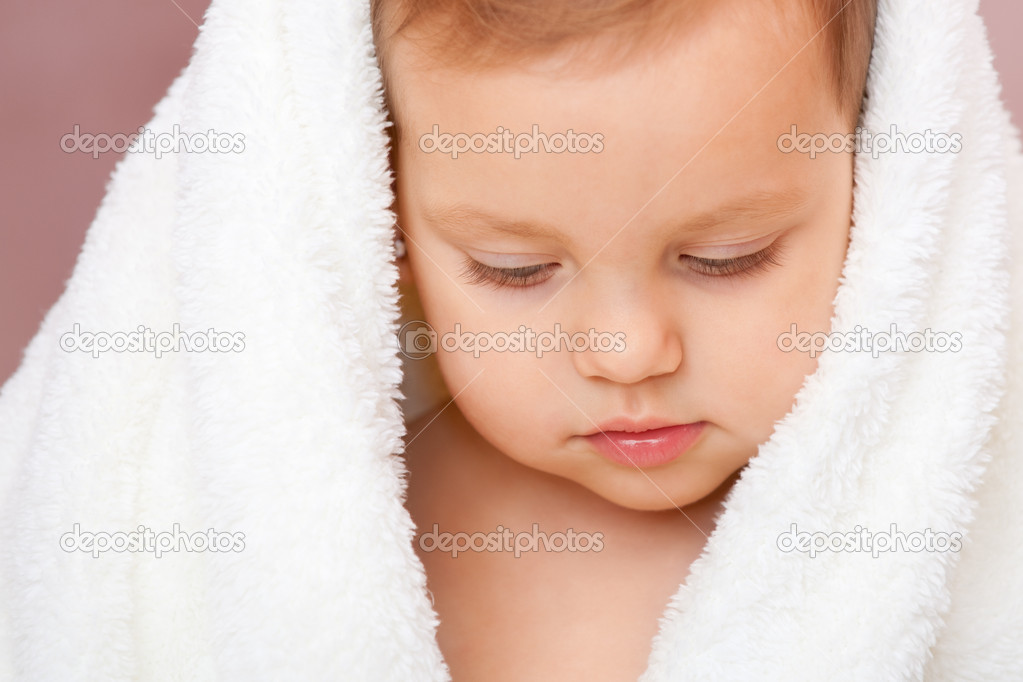 A shy little girl covered with a snow white bath towel is looking down after having shower — Stock Photo #8144243