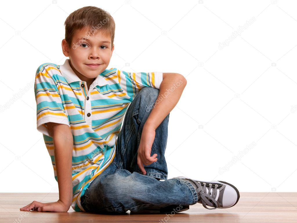 A handsome kid is smiling sitting on the wooden background isolated on white — Stock Photo #8144393