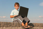Smiling boy holding a laptop — Stock Photo