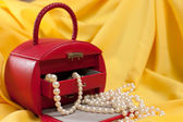 Red jewellery case on the yellow background — Stock fotografie