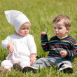 Two toddlers on the green grass - Stock Photo