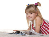 Smiling girl reading on the white thick carpet — Stock Photo