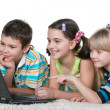 Three kids reading internet information using a laptop — Stock Photo