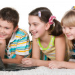 Three cheerful kids are using a laptop — Stock Photo