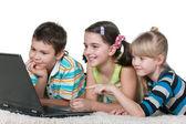 Three kids reading internet information using a laptop — Stock Photo
