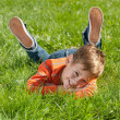 Smiling boy lying on the grass - Stock Photo