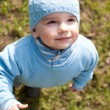 Portrait of a kid in blue walking in the spring meadow — Stock Photo