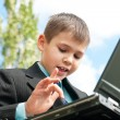 Schoolboy studies outside — Stock Photo