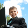 Boy with laptop studies outside — Stock Photo