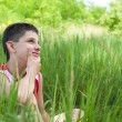 Thoughtful boy in the green grass — Stock Photo