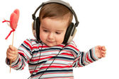 Kid in striped shirt with headphones and red heart — Stock Photo