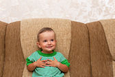 Smiling little boy on the sofa — Stock Photo