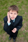 Serious boy in suit speaking over the mobile — Stock Photo