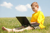 Smart boy with a laptop on the grass — Stock Photo