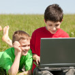 Two boys with laptop on the grass — Stock Photo