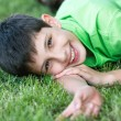 Smiling boy in green on the summer meadow — Stock Photo