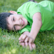 Happy boy in green lying on the green glade - Stock Photo