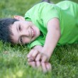 Happy boy in green lying on the green glade — Stock Photo #8658931