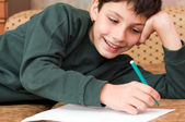 Smiling boy writes a letter — Stock Photo