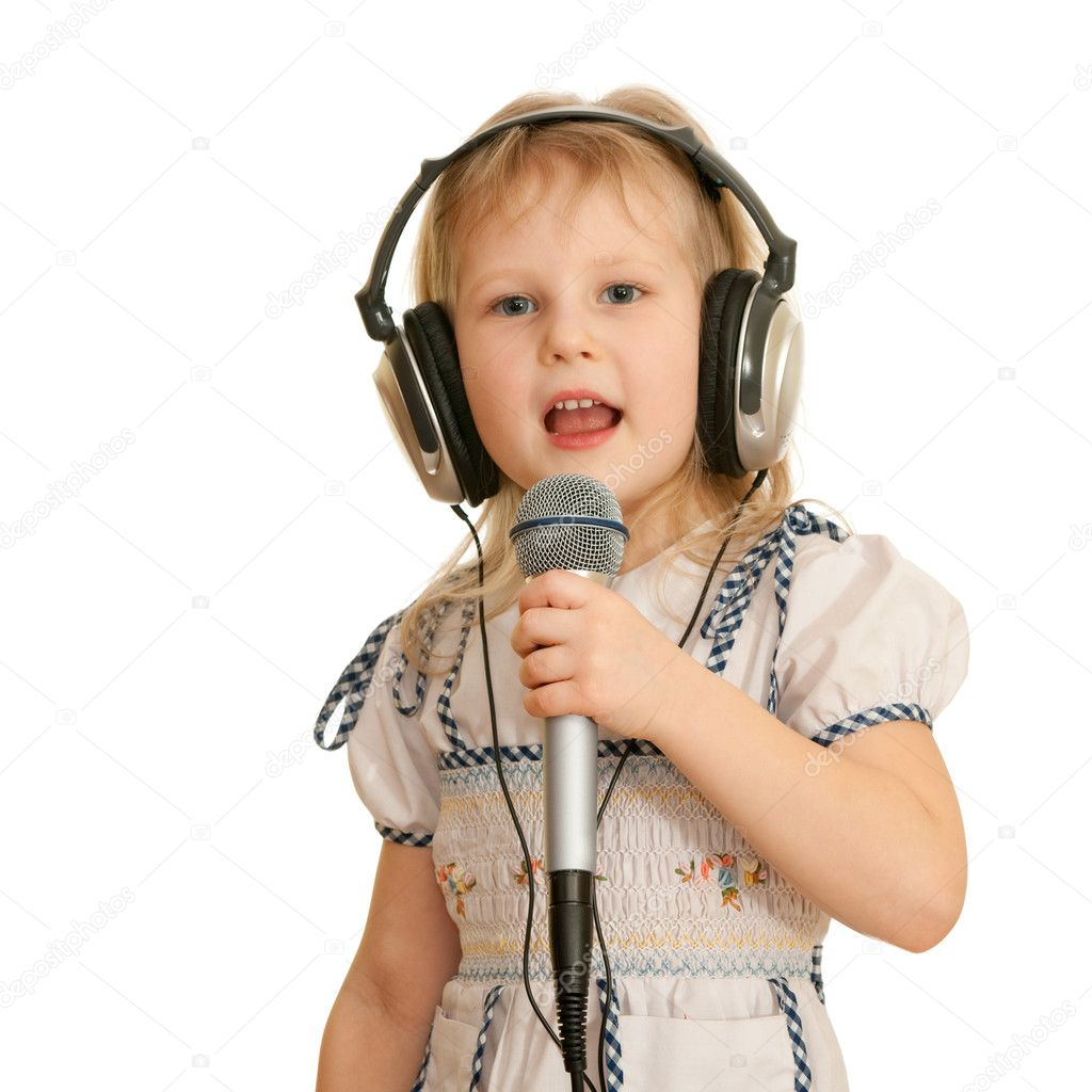 cheerful little girl in headphones holding a microphone is singing a