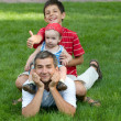 Two sons are sitting on their father's back — Stock Photo