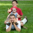 Stock Photo: Two sons are sitting on their father's back