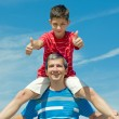 Child in a red shirt sitting on his father — Stock Photo