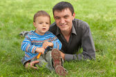 Portrait of dad and son against the green grass — Stock Photo