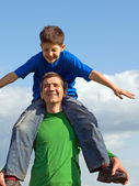 A man is handing his happy son outdoors — Stock Photo