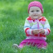 Kid in pink sitting on the green meadow — Stock Photo