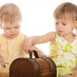 Two little blonde girls playing with a wooden chest — Stock Photo