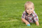 緑の草に面白い小さな男の子 — ストック写真