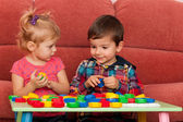 Boy and girl playing at the table — Stock Photo