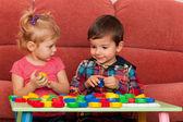 Niño y niña jugando en la mesa — Foto de Stock