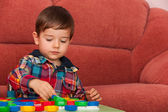 Serious little boy playing at the table — Stock Photo