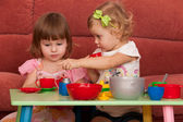 Little girls playing at the table — Stock Photo