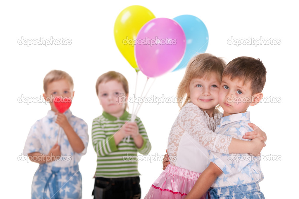 A cheerful laughing girl cuddles a little boy; his two friends are holding a red heart and vivid baloons; isolated on the white background  Stock Photo #8721722